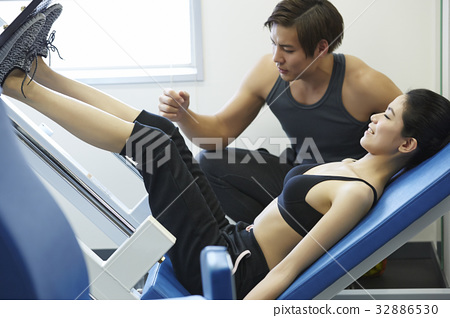 Instructor is assisting a woman with leg exercise. 32886530