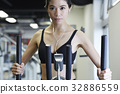portrait of young woman using exercise machine in fitness center 32886559