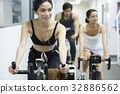 Three happy people are training on exercise bike indoors 32886562