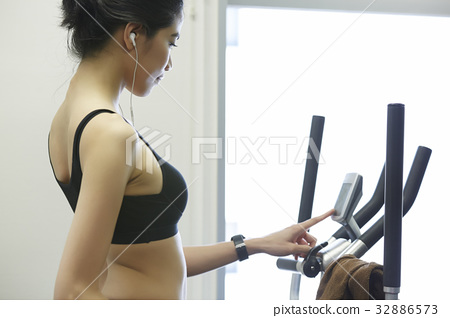 A woman wearing earphone is adjusting in the treadmill 32886573