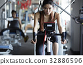 A slim and heathy woman is riding bicycle in the fitness club 32886596