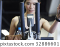 Woman is looking curiously at the screen of treadmill 32886601