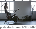 Woman is listening to music while riding bike in fitness club 32886602