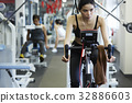 The woman is looking someone when riding bike in fitness club 32886603
