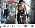 a beautiful woman is cycling and listening to music in the gym 32886607