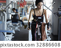 a beautiful woman is cycling and looking at something in the gym 32886608