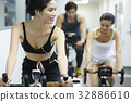 a group of three people is working out on the exercise bike at the gym 32886610