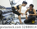 male coach is training to woman with dumbbell 32886614