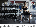 woman is lifting dumbbells and looking at something in gym 32886631