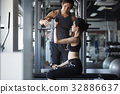 fit woman is lifting dumbbells with her coach 32886637
