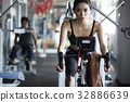 a portrait of a fit woman cycling in gym center 32886639