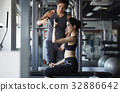 coach is assisting young woman in lifting dumbbells in fitness club 32886642