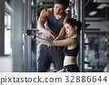 A man is guiding a woman how to use the machine at a fitness center 32886644