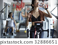 A woman is drinking water after doing exercise at fitness center 32886651