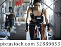 A woman is riding with auto bike at fitness center 32886653