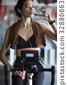 A girl is drinking water after riding auto bike at fitness center 32886663