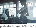 A woman is doing exercise with modern machine at fitness center 32886673