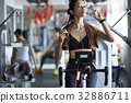 a portrait of woman using the bike and drinking water 32886711