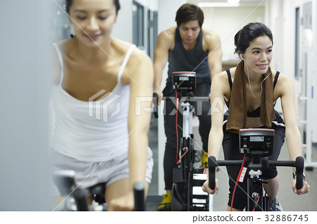 The picture of three people riding the exercise bike in a fitness club 32886745