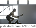 a woman is riding a bike in a gym center 32886748