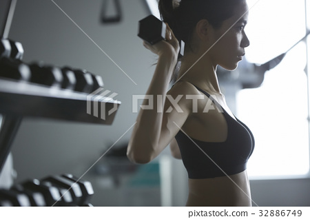 a portrait of a woman lifting the dumbbell over the shoulder 32886749