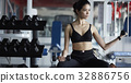 The portrait of a woman lifting dumbbells in the gym 32886756