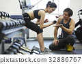 A photo of Thai instructor instructing a women to lift dumbbells in a gym. 32886767