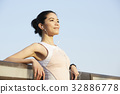 A young woman is enjoying fresh air while listening to music. 32886778