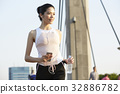 A Thai woman is listening to music while jogging in the morning. 32886782