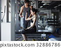 A Thai instructor is training weight lifting for a woman in a gym. 32886786