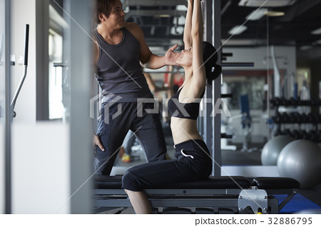 A photo of young woman is raising both hands to practice to lift weights. 32886795