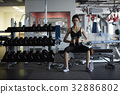 a photo of a woman doing gymnastics while sitting at a gym. 32886802