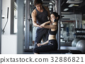 a photo of a trainer guiding a woman doing gymnastics. 32886821