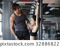 a photo of a man guiding a woman working out at a fitness center 32886822