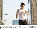 a girl is resting and looking at her watch when jogging 32886850