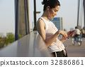 a woman in sportswear is standing and using her phone 32886861
