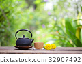 Old black tea pot with brown cup and flower 32907492