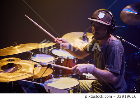 Performance of the rock band.. Drummer 32919616