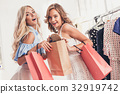 The two young pretty girls looking at dresses and 32919742