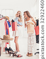 The two young pretty girls looking at dresses and 32922460