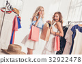 The two young pretty girls looking at dresses and 32922478