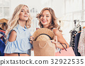 The two young pretty girls looking at dresses and 32922535