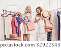 The two young pretty girls looking at dresses and 32922543