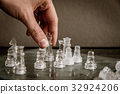 Hand moving the queen on the glass chessboard 32924206