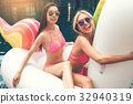 Young women friends in the swimming pool fun 32940319
