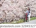 桜並木をサイクリングする女性 32945327