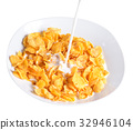 pouring milk into bowl of corn flakes 32946104