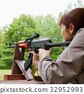 woman shooting an automatic rifle for strikeball 32952993