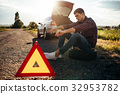 Broken car concept, man sitting on tire 32953782