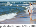Young woman walking on white sand to beautiful beach, Baltic Sea, Poland 32955188